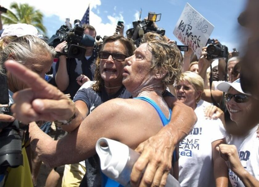 Endurance swimmer Diana Nyad, right, and her trainer Bonnie Stoll hug after Nyad walks ashore in Key West, Fla. after swimming from Cuba.