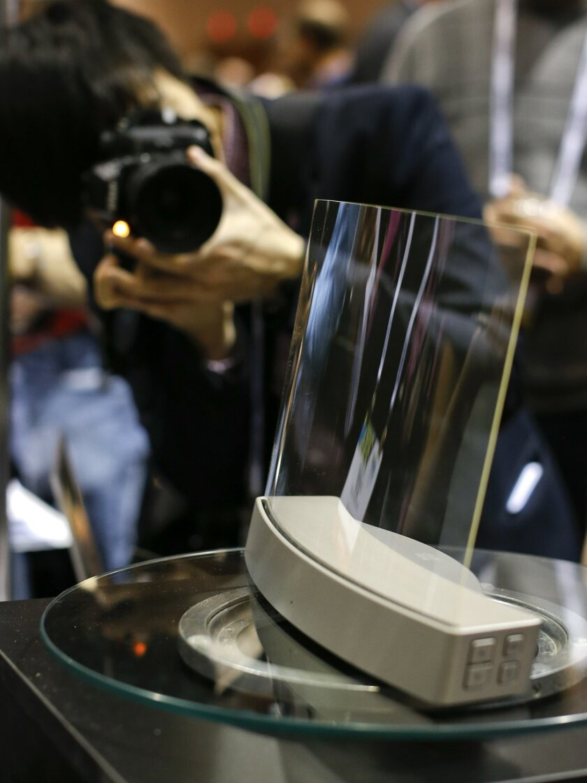Members of the media photograph a glass speaker called Clio during the International Consumer Electronics Show, Sunday, Jan. 5, 2014, in Las Vegas. The speaker, produced by ClearView Audio uses a single piece of curved millimeter-thick acrylic glass that sits on a dock which vibrates it in a finely tuned way so that it can play music. It works with Bluetooth streaming and with a 3.5 millimeter jack. (AP Photo/Julie Jacobson)