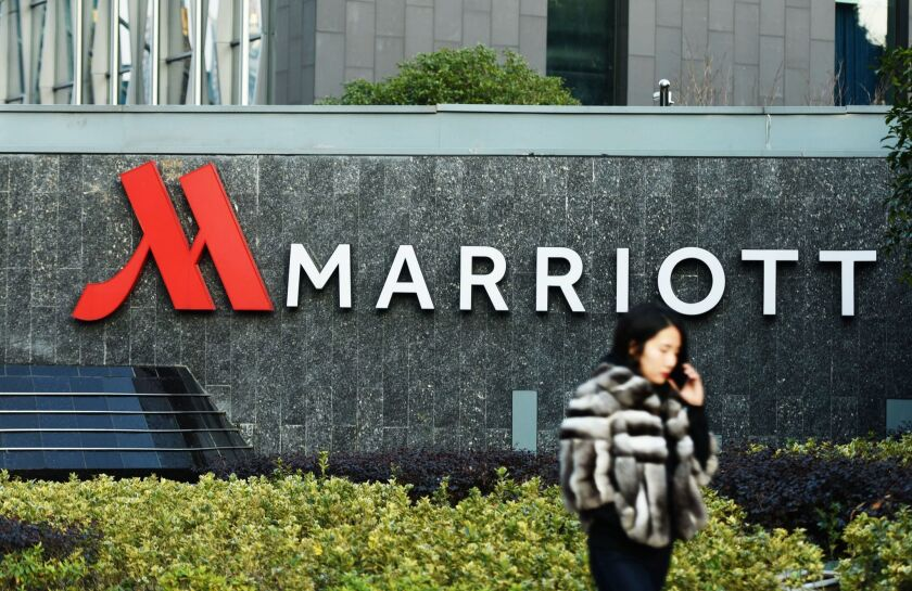 This photo taken on January 11, 2018 shows a woman walking past Marriott signage in Hangzhou in China's Zhejiang province. Authorities in China have shut down Marriott's local website for a week after the U.S. hotel giant mistakenly listed Chinese-claimed regions such as Tibet and Hong Kong as separate countries.