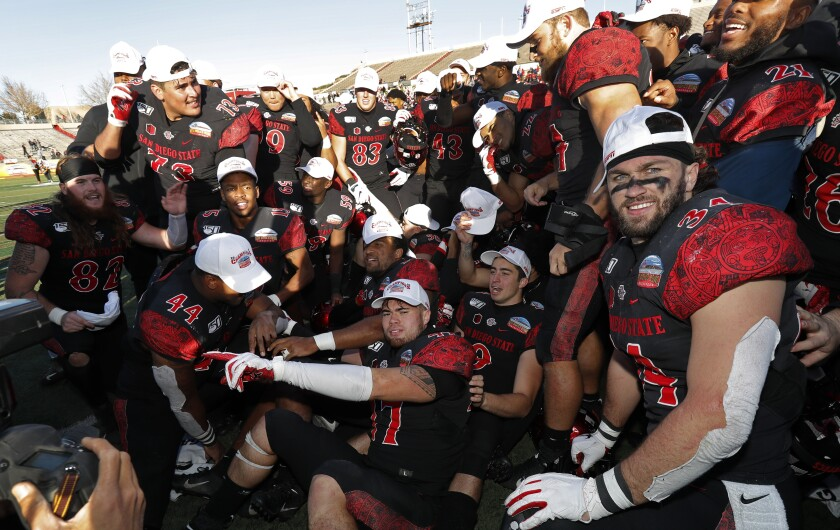 San Diego State football players celebrate on the field at Dreamstyle Stadium after Saturday's 48-11 win over Central Michigan in the New Mexico Bowl.