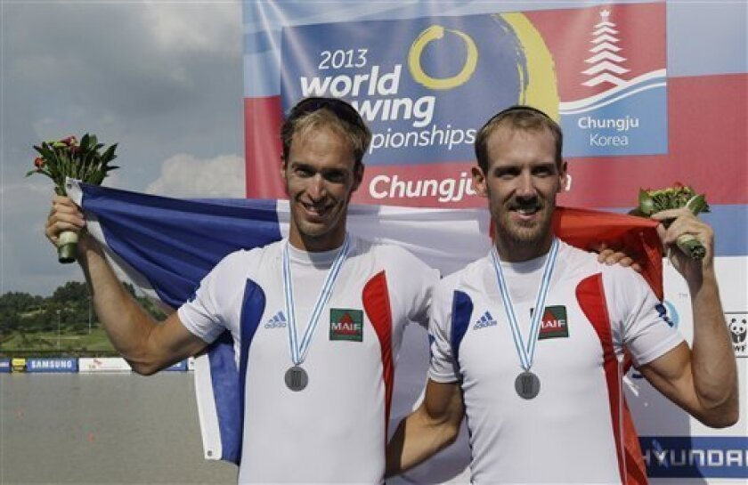 Silver medal winners Germain Chardin, left, and Dorian Mortelette of France pose for photos during a medal ceremony for the men's pair final event of the World Rowing Championships in Chungju, south of Seoul, South Korea, Saturday, Aug. 31, 2013. (AP Photo/Lee Jin-man)