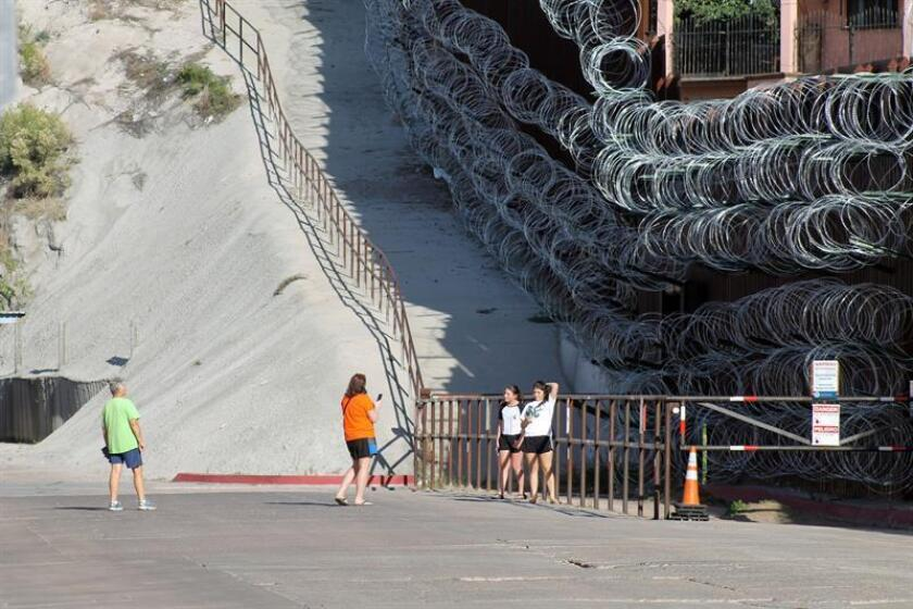 A photograph taken on March 24, 2019, shows a group of people posing for photos in front of the razor wire placed along the US-Mexican border in Nogales, Arizona. EPA-EFE/Paula Diaz
