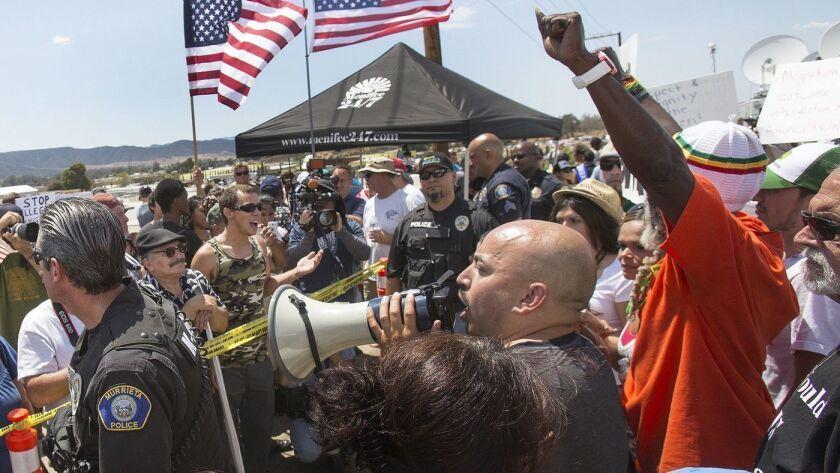 La policía separa a grupos de manifestantes fuera del Centro de Detención de la Patrulla Fronteriza en Murrieta en 2014. (Gina Ferazzi / Los Angeles Times)