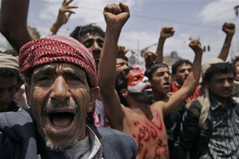An elderly anti-government protestor, left, shouts slogans along with other demonstrators during a demonstration demanding the resignation of Yemeni President Ali Abdullah Saleh, in Sanaa, Yemen, Saturday, June 4, 2011. Five top members of the government were sent to Saudi Arabia for treatment of wounds they suffered in a rebel rocket attack on the presidential palace, the official government news agency reported Saturday. President Ali Abdullah Saleh was slightly injured. (AP Photo/Hani Mohammed)