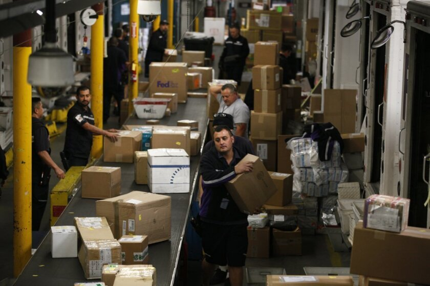 U-T File: This Dec. 10, 2012 file photo shows FedEx employees working on the busiest shipping day of the year, CyberMonday. Retailers this year are competing for online business with early free-shipping offers.