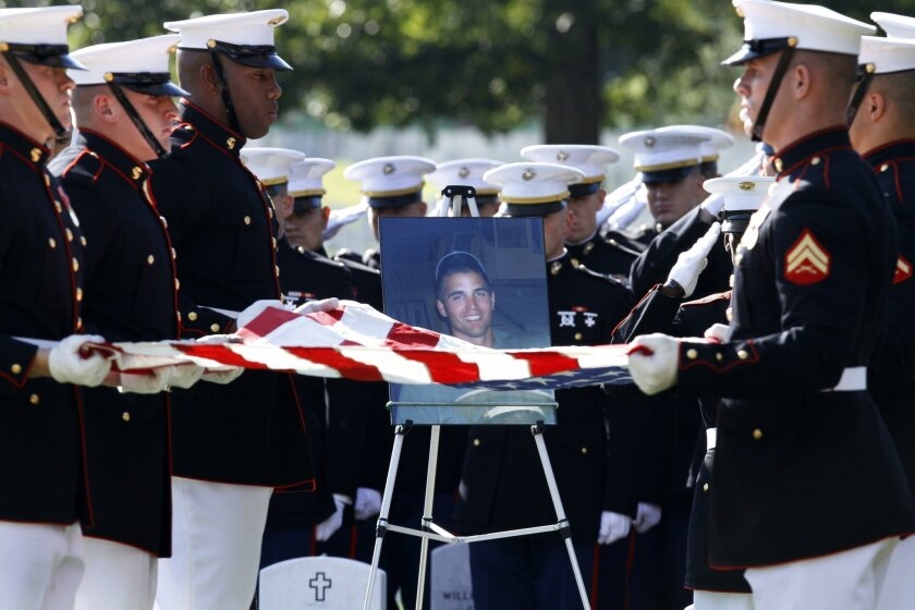Members of the Marine Corps Honor Guard fold the flag over the grave of 1st Lt. Travis Manion at Arlington National Cemetery in Arlington, Va., on Oct. 1, 2010. He is buried next to his best friend, Marine Corps Lt. Brendan Looney.