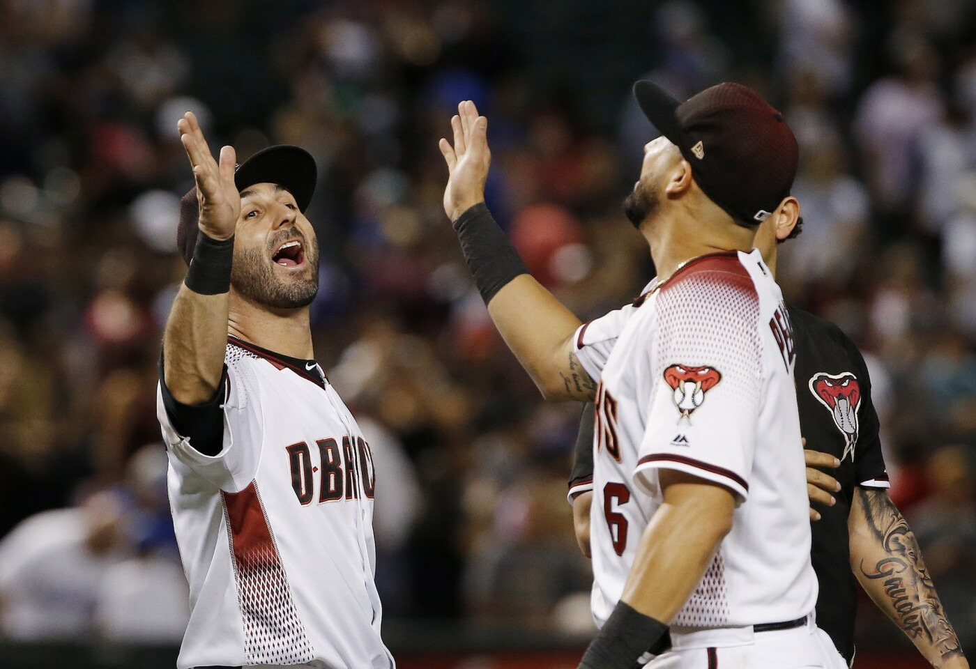 Arizona Diamondbacks' David Peralta, right, gives a high-five to Daniel Descalso after the team's baseball game against the Los Angeles Dodgers on Wednesday, Sept. 26, 2018, in Phoenix. The Diamondbacks defeated the Dodgers 7-2. (AP Photo/Ross D. Franklin)