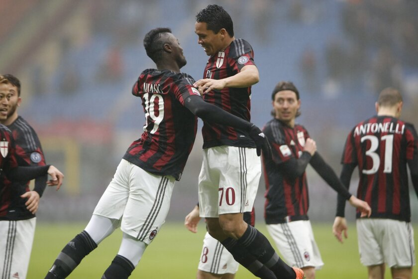 AC Milan's Carlos Bacca, right, celebrates with his teammate Mbaye Niang after scoring during a Serie A soccer match between AC Milan and Genoa, at the San Siro stadium in Milan, Italy, Sunday, Feb. 14, 2016. (AP Photo/Luca Bruno)
