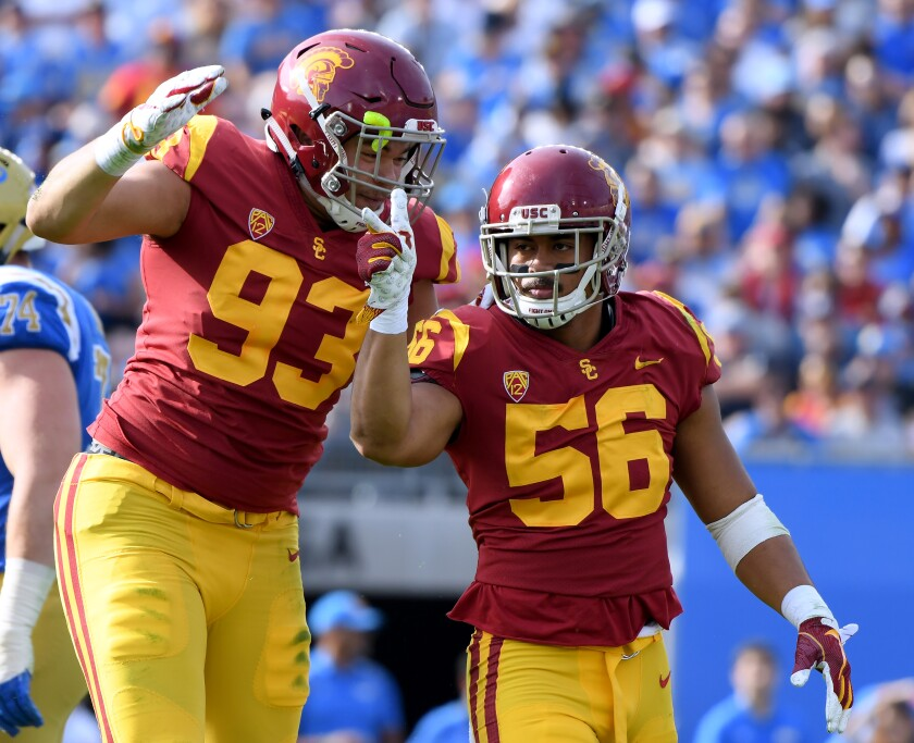Jordan Iosefa (56) celebrates a sack with Liam Jimmons (93) during the first half of a game against the UCLA on Nov. 17, 2018 at the Rose Bowl.