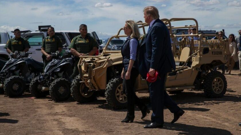 President Trump walks with Homeland Security Secretary Kirstjen Nielsen in Calexico, Calif., on Friday. She was ousted from her post two days later.