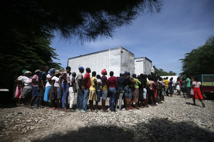 People wait near the front of a line hundreds of people long for government distributed food and school supplies to some residents of the Cite Soleil slum, in Port-au-Prince, Haiti, Thursday, Oct. 3, 2019. The administration of President Jovenel Moise tried to alleviate Haiti's economic crunch on Thursday by distributing plates of rice and beans, sacks of rice, and school backpacks filled with four notebooks and two pens. (AP Photo/Rebecca Blackwell)