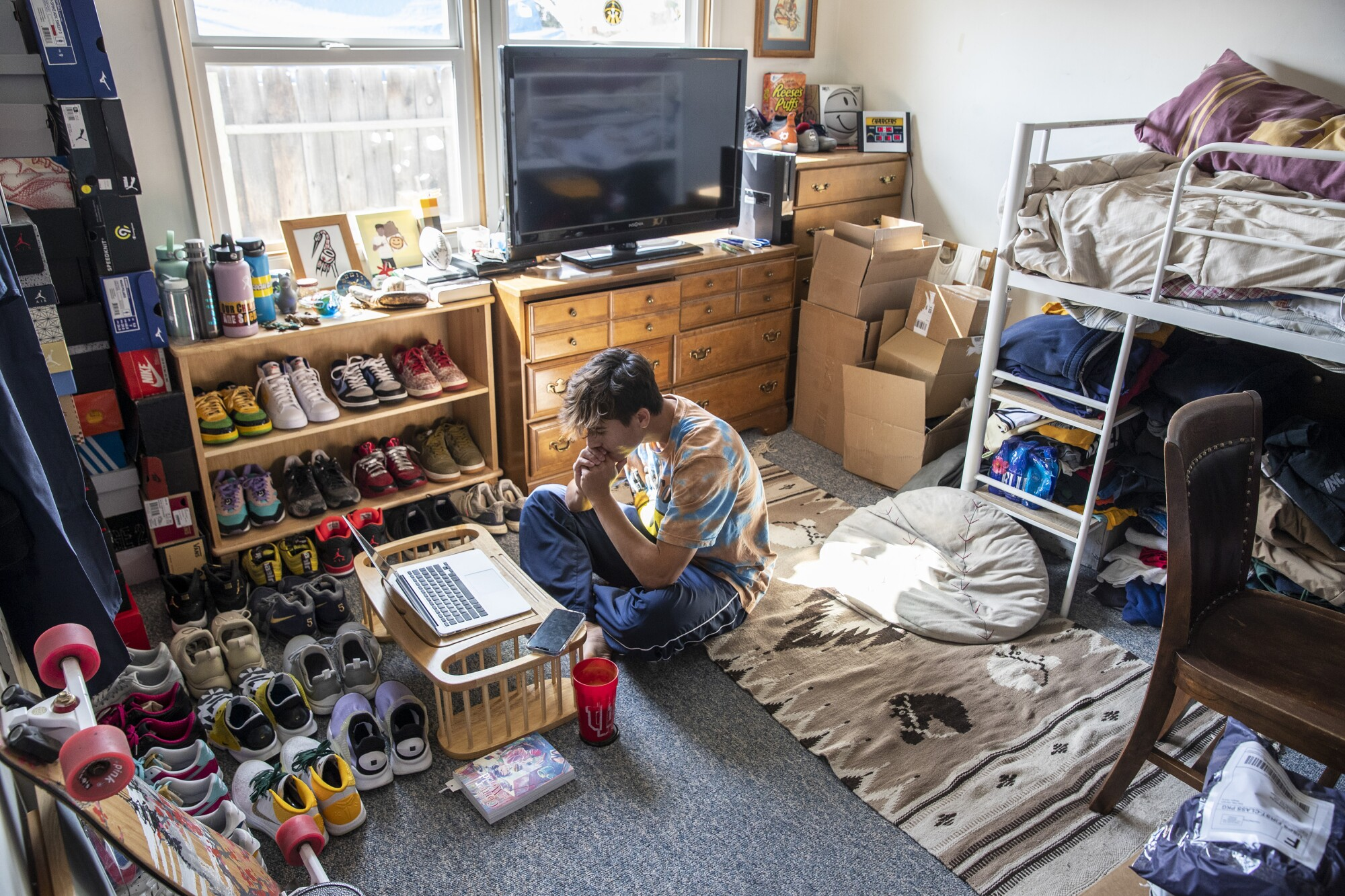 A student sits on the floor of his bedroom watching an online class.