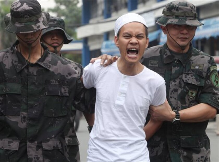 """Dino Amor Pareja also known as Khalil Pareja, center, a ranking leader of the al-Qaida-linked terror group Rajah Solaiman Movement, shouts """"Allahu Akbar"""" (God is Great!) as he is escorted to his detention cell following an announcement of his capture by Philippine National Police Chief Jesus Versoza, unseen, at Camp Crame at suburban Quezon city northeast of Manila, Philippines Tuesday Aug. 25, 2009. Pareja, who carries a combined US$100,00 reward for his capture from U.S. and Philippine governments, was arrested Friday in Marawi city in southern Philippines. (AP Photo/Bullit Marquez)"""