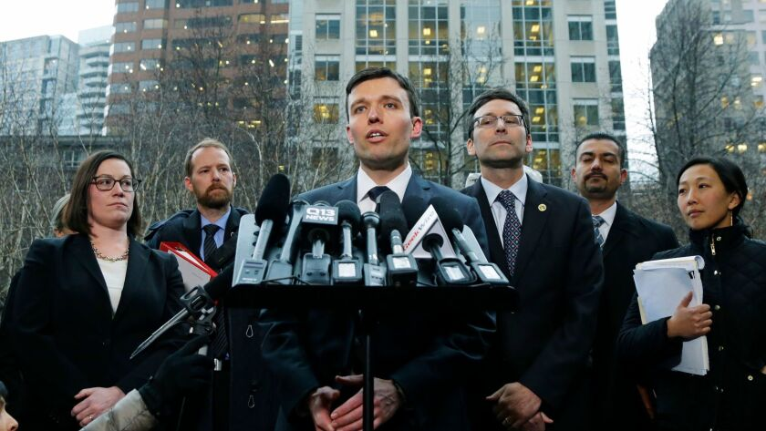 Washington state Solicitor General Noah Purcell, center, addresses reporters about the state's lawsuit against the Trump administration following a hearing in federal court in Seattle on Feb. 3.