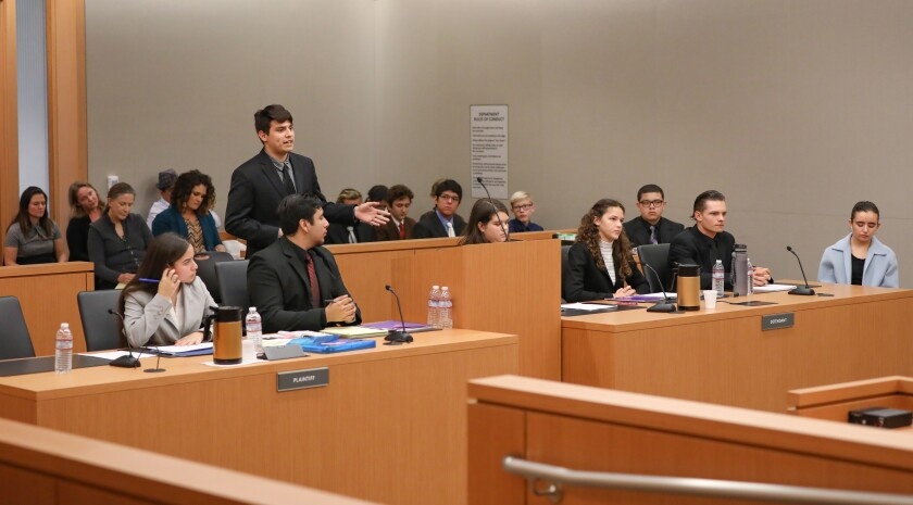 Jose Beltran, of the King-Chavez Community High School team, standing, and acting for the prosecution, addresses the court during the 14th annual San Diego County High School Mock Trial Competition at the San Diego Superior Court on Saturday. They competed against the Coastal Academy team.