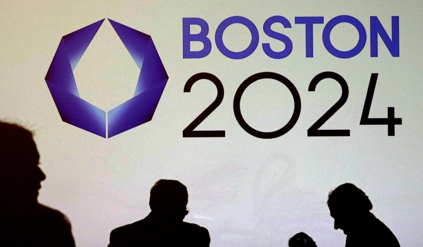 Shadows of organizers and reporters pass a video display screen on Jan. 21 prior to a news conference by organizers of Boston's campaign for the 2024 Summer Olympics in Boston.
