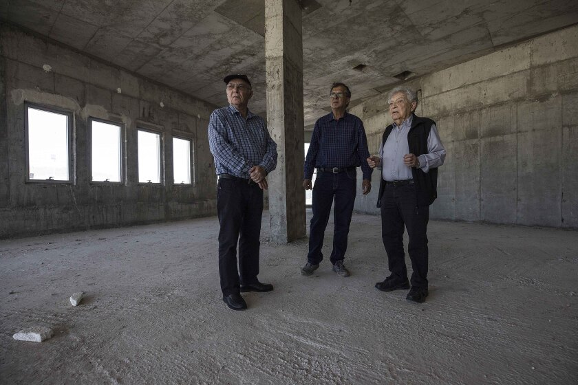 FILE - In this Tuesday, April 18, 2017 file photo, Jewish World War II veterans Chaim Erez, left, Zvi Kan-Tor, center, and Yitzhak Arad stand during an interview with The Associated Press inside the unfinished museum honoring Jewish World War II veterans, in Latrun, Israel. Arad, a Holocaust survivor and scholar who was the director of Israel's Yad Vashem Holocaust memorial for more than two decades, has died at the age of 94, Thursday, May 6, 2021. (AP Photo/Tsafrir Abayov, File)
