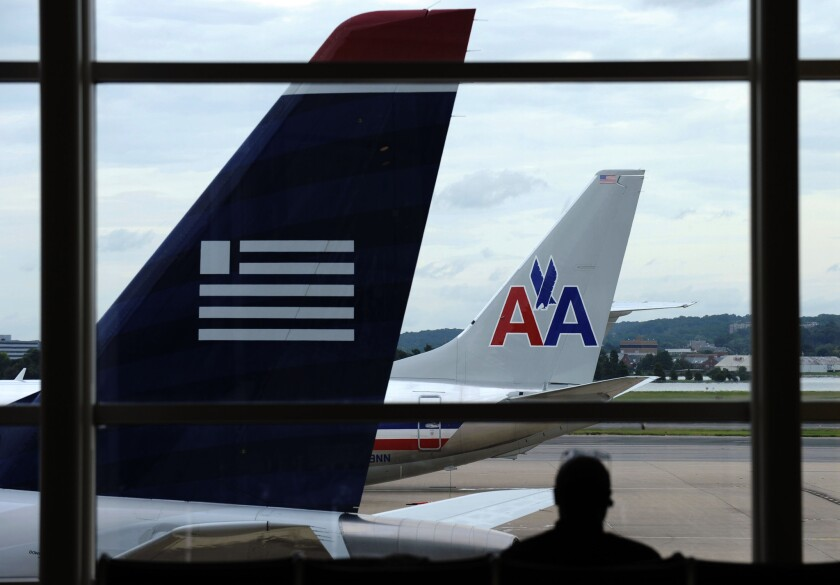 An American Airlines plane and a US Airways plane are parked at Washington's Ronald Reagan National Airport in Washington.