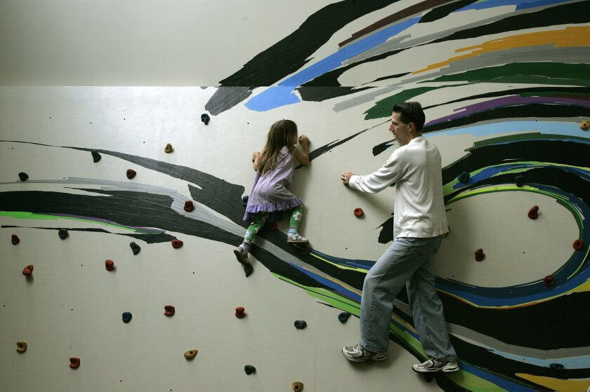 Adam DiProfio (right) and his 4-year-old daughter, Diana, play on a rock climbing wall at the New Children's Museum in downtown San Diego.