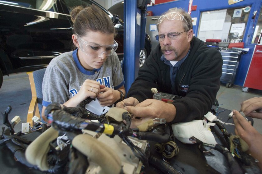 Auto mechanics teacher Robert Grace (right) assists student Alexia Hall as she practices for National Automotive Technology Challenge.