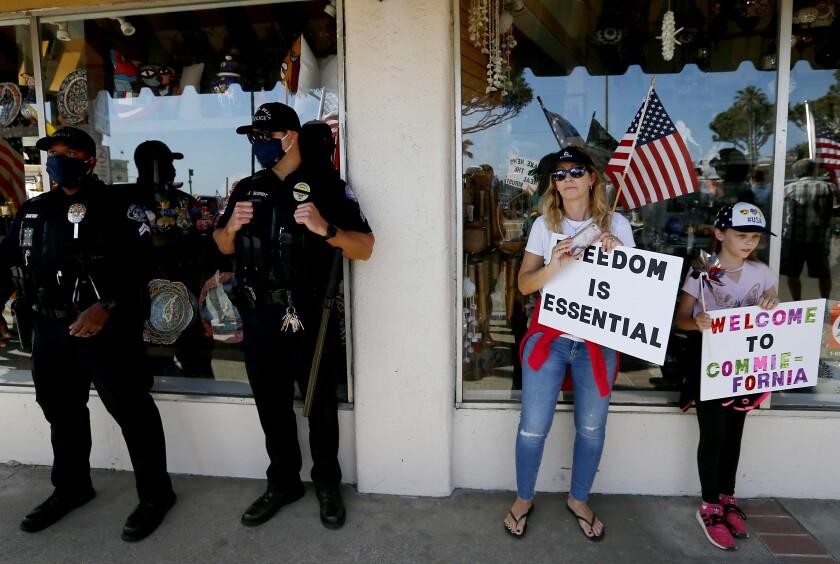 Policías y manifestantes se protejen del sol el sábado en Pacific Coast Highway en Laguna Beach.