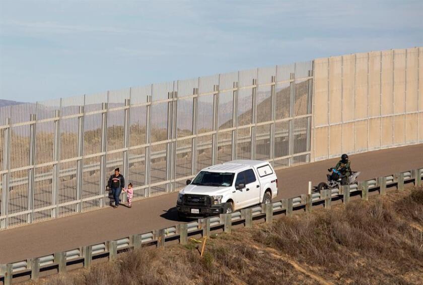 Una mujer migrante es detenida por la policía estadounidense en el muro fronterizo de la ciudad de Tijuana, en Baja California (México). EFE/Archivo