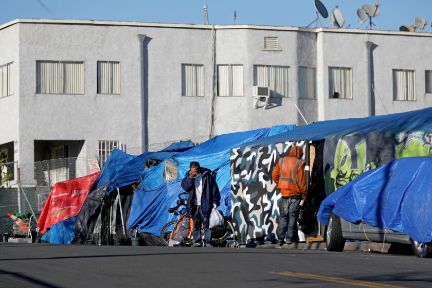 Two men stand outside tents and tarps on an urban sidewalk