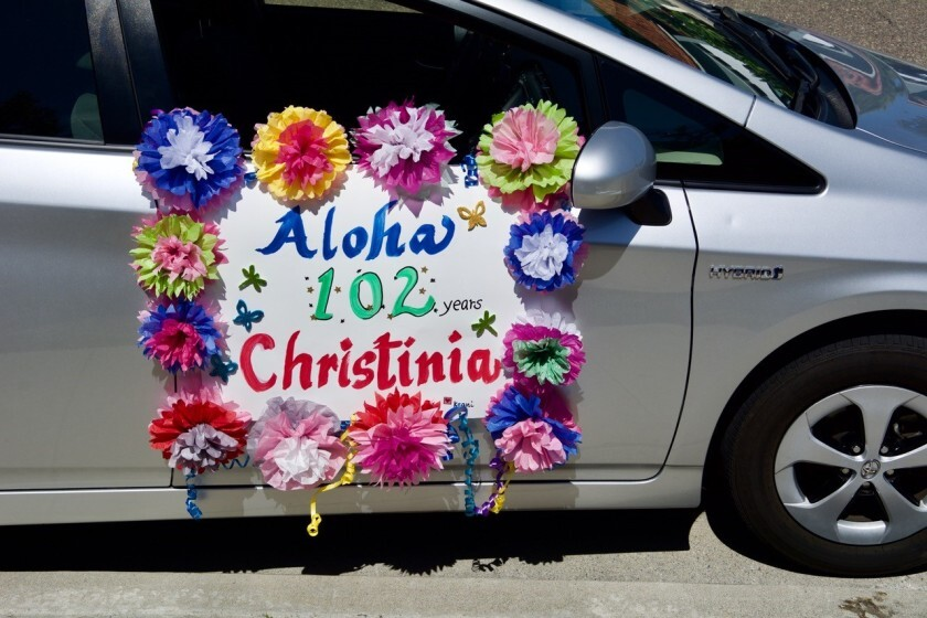 A car drives by Christinia Lee's 102nd birthday party.