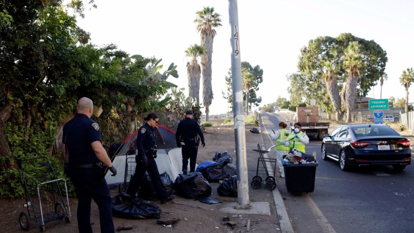 Police remove a tent during an operation in San Diego to sanitize neighborhoods frequented by the homeless to control the spread of hepatitis A.