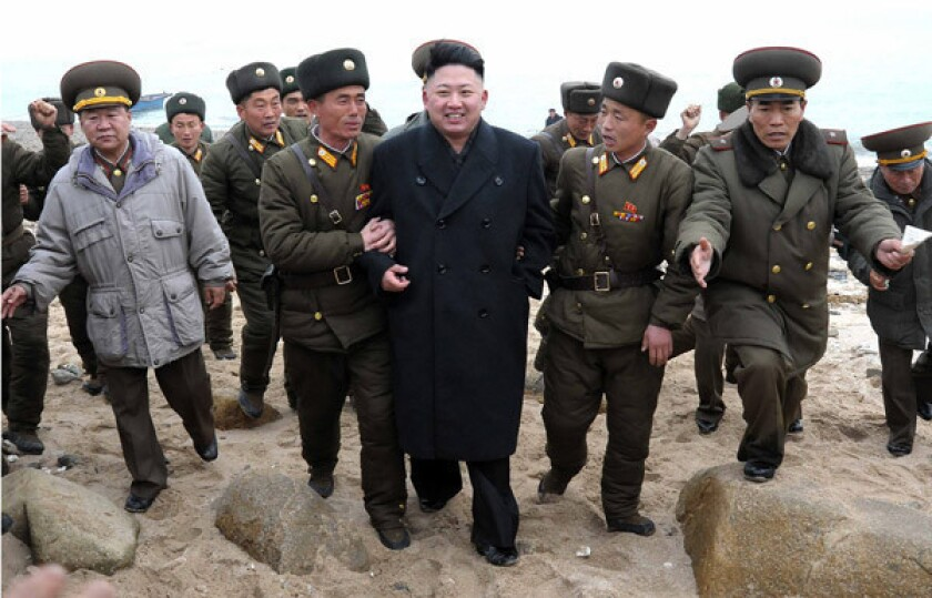 North Korean leader Kim Jong Un, center, walks with military personnel as he arrives to inspect a military unit on Mu Islet, near the border with South Korea.
