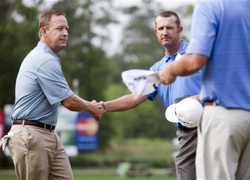 Jeff Maggert, left, shakes hands with David Mathis after finishing the second round in the Houston Open golf tournament, Saturday, March 31, 2012, in Humble, Texas. (AP Photo/Eric Kayne)