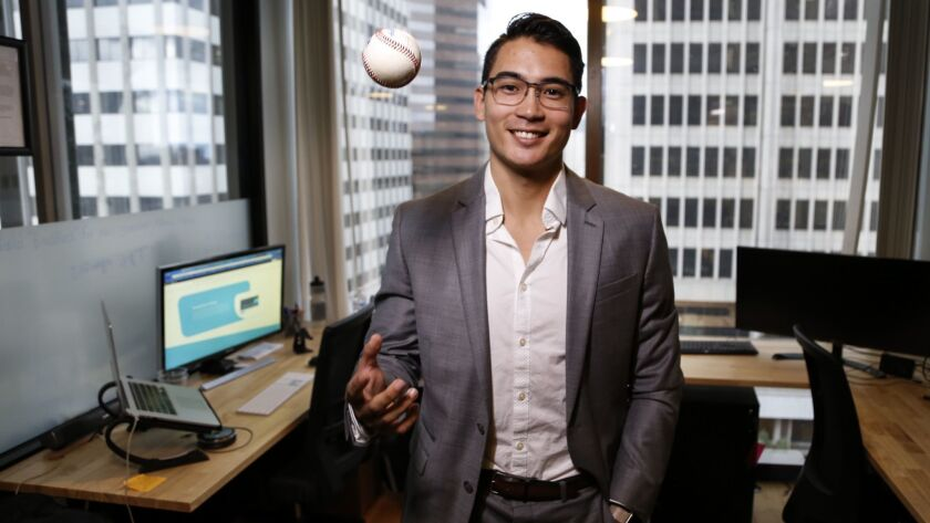 Former San Diego State baseball player Tyler Adkison tosses a ball in his downtown office. Adkison, 23, walked away from a minor league career with the Dodgers organization last spring to start his own investment company called BlockTerra Capital.
