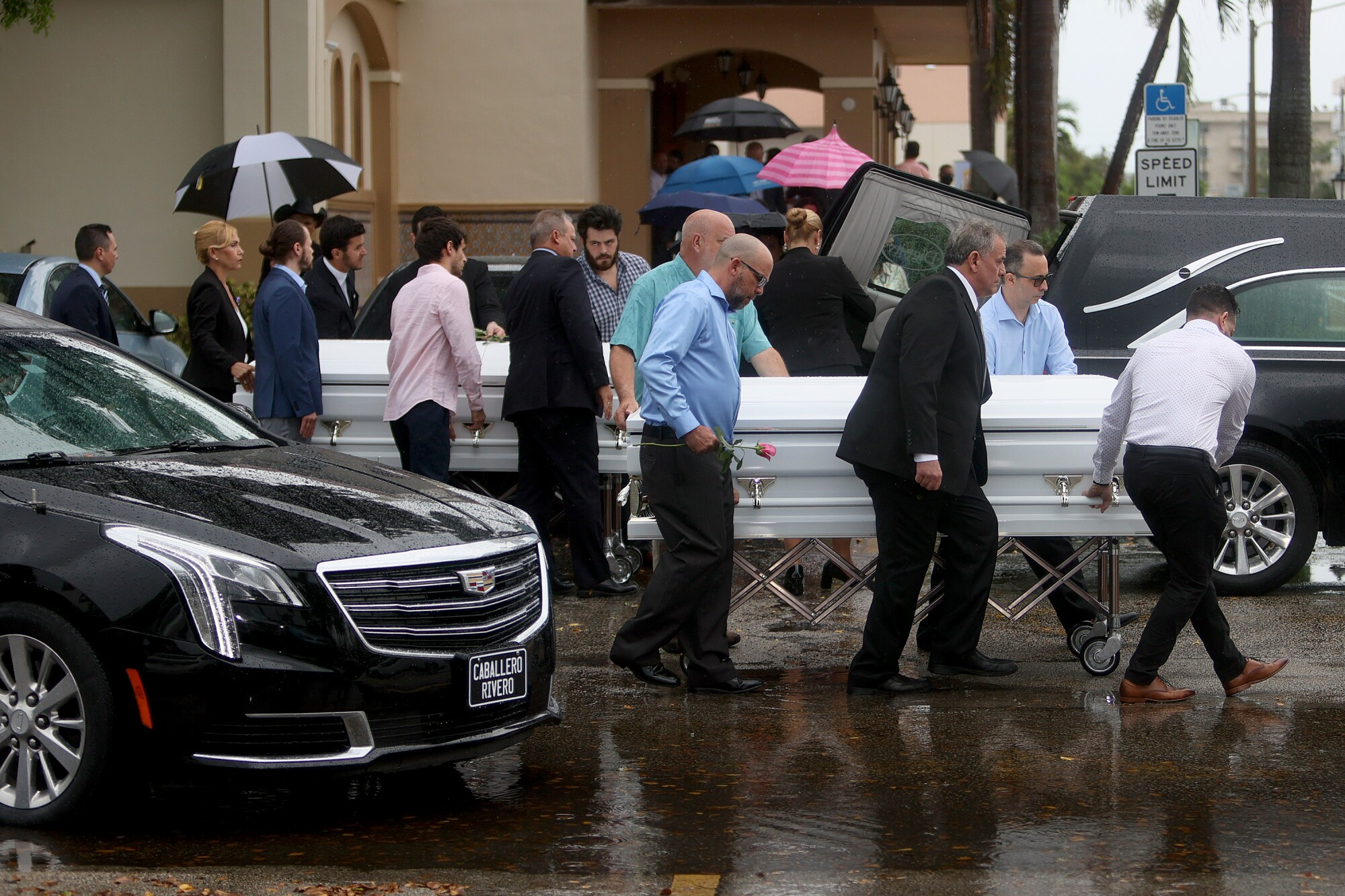 Pallbearers bring caskets to the hearse after the funeral at St. Joseph Catholic Church.