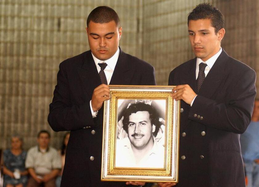 """Michael """"Mickey"""" Munday, piloto del fallecido capo colombiano Pablo Escobar, fue hallado hoy en Miami culpable de fraude postal como parte de una red de contrabando y robo de unos 150 vehículos. en la imagen del 30 de noviembre de 2003 dos jóvenes no identificados sostienen una fotografía del extinto capo del narcotráfico Pablo Escobar Gaviria. EFE/ARCHIVO"""