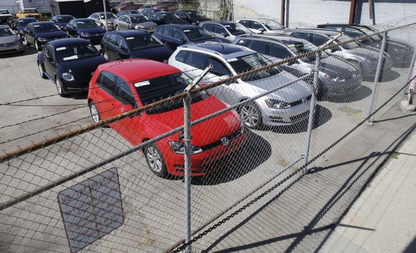 Volkswagen diesels are shown behind a security fence on a storage lot near a VW dealership in Salt Lake City.