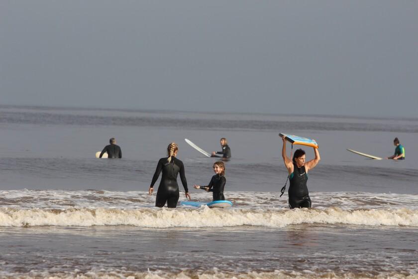 Surfers hit the water off La Jolla Shores on April 27.