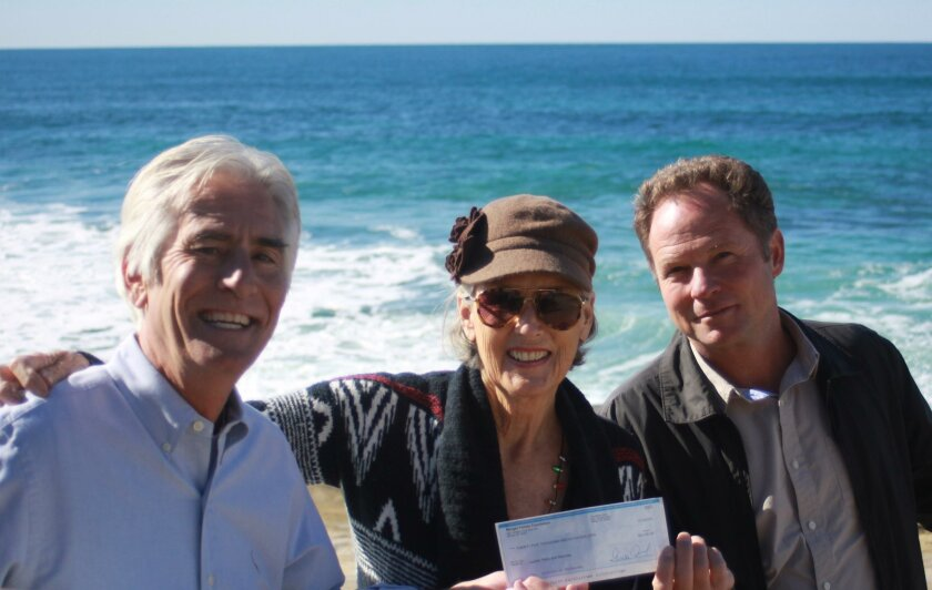 Tom Morgan hands over $25,000 to complete the WindanSea S-Curve project to Melinda Merryweather and Jim Neri.