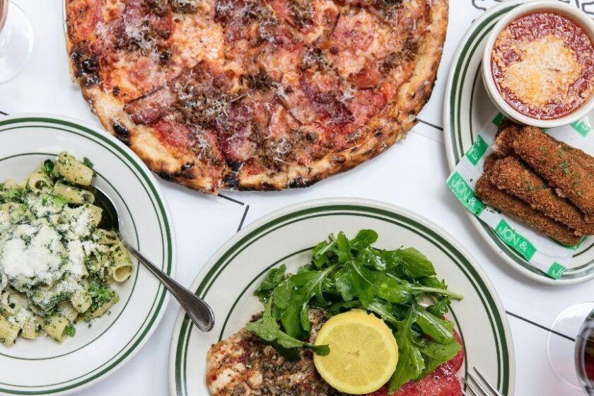 LOS ANGELES, CALIFORNIA - APR. 30, 2019: A lunch spread at Jon & Vinny's, including Roman Gladiator pizza with bacon, Italian sausage, pepperoni, and smoked ham; mozzarella sticks in Italian breadcrumbs served with spicy pomodoro; grilled chicken with olive, heirloom tomato, arugula and lemon; and rigatoni with broccolini, garlic, chilies and pecorino romano; on Tuesday, Apr. 30, 2019, at the second installment of the Italian restaurant, in Brentwood. (Photo / Silvia Razgova) 3078377_la-fo-bill-addison-jon-and-vinnys-review