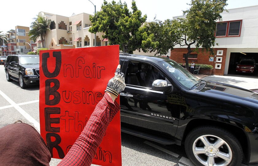 Uber drivers and supporters gather to protest outside of Uber offices in Santa Monica on Tuesday.