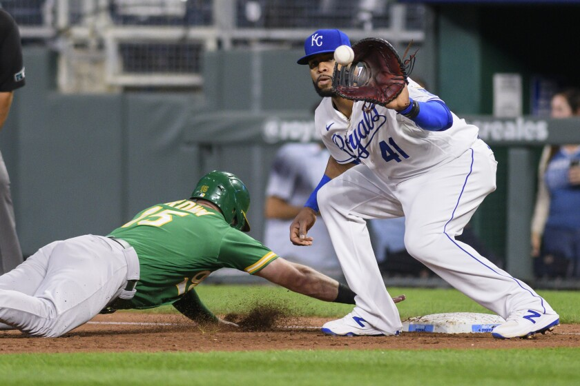 The Oakland Athletics' Seth Brown dives back ahead of the throw to Kansas City Royals first baseman Carlos Santana during the second inning of a baseball game, Tuesday, Sept. 14, 2021 in Kansas City, Mo. (AP Photo/Reed Hoffmann)