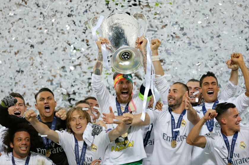 Real Madrid's Sergio Ramos celebrates with the trophy after the Champions League final soccer match between Real Madrid and Atletico Madrid at the San Siro stadium in Milan, Italy, Saturday, May 28, 2016. Real Madrid won 5-4 on penalties after the match ended 1-1 after extra time.   (AP Photo/Manu