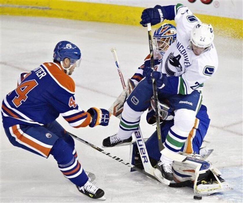 Vancouver Canucks' Daniel Sedin (22) is stopped by Edmonton Oilers goalie Devan Dubnyk , back right, as Oilers' Corey Potter, left, looks for the rebound during first-period NHL hockey game action in Edmonton, Alberta, Saturday, March 30, 2013. (AP Photo/The Canadian Press, Jason Franson)