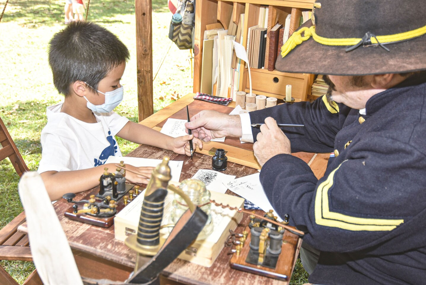 Holden Cheng learning how to write with a dip pen and ink well under the guidance of reenactor Joe Mortimer.