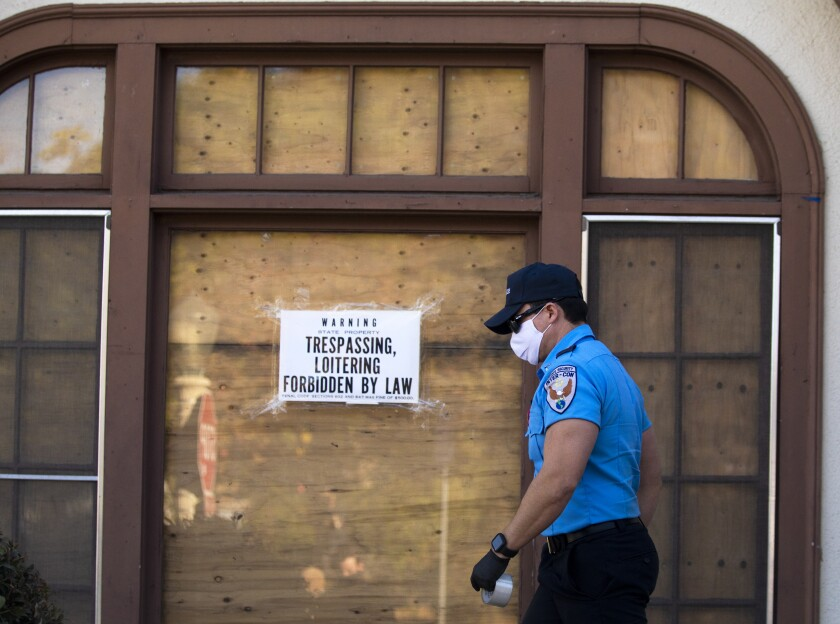 A security worker tapes up warning signs against trespassing at a  vacant home in the El Sereno neighborhood