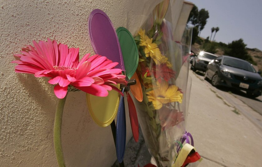 People have left flowers and other tributes by the Parkcreek Court house in San Diego's Skyline neighborhood where a family of four was found dead Tuesday in an apparent murder-suicide.