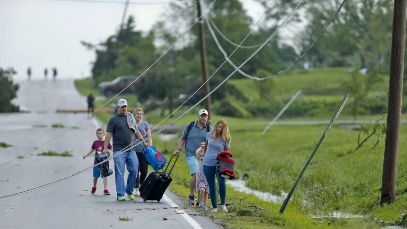 A family ducks under power lines as they make their way out of a tornado damaged neighborhood after