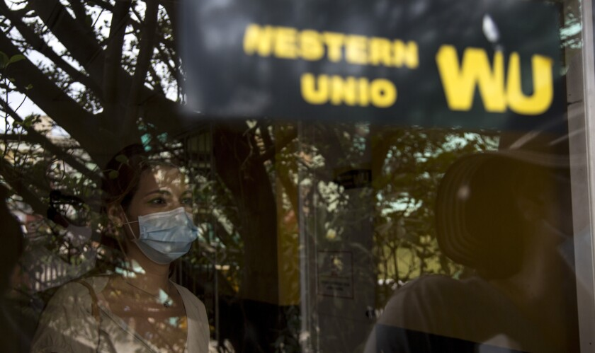 Photographed through a window, a woman waits to collect money at a Western Union office on its last day of business in Havana, Cuba, Monday, Nov. 23, 2020. Restrictions from the Trump administration on the military-controlled operator that handles cash deposits will go into effect Monday at 6 p.m. local, keeping Cubans from being able to retrieve money sent from abroad through Western Union – the main source of cash remittances for many families. (AP Photo/Ismael Francisco)