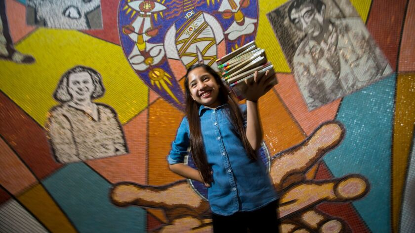 """Leilany Medina, 11, holds a stack of books from her favorite series, """"Judy Moody,"""" at the East Los Angeles Library, where she """"read away"""" late fees last week. Students won't have to worry about new late fees because of just-approved library rules."""
