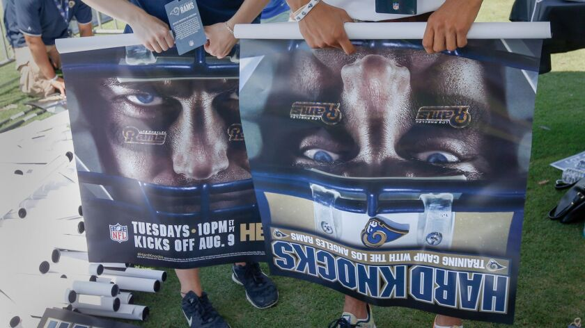 """Rams employees roll """"Hard Knocks"""" posters to be handed out to the fans at practice on Aug. 2."""