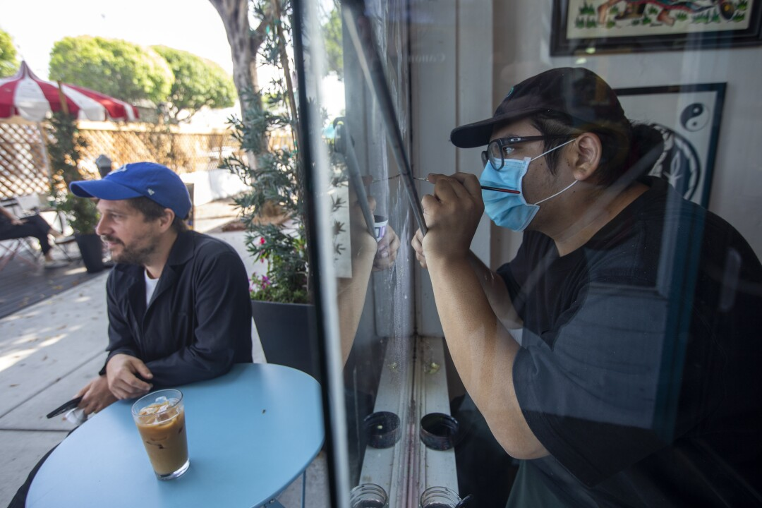 An unmasked man sits at an outdoor table with an iced coffee as another man wearing a mask paints the inside of a shop window